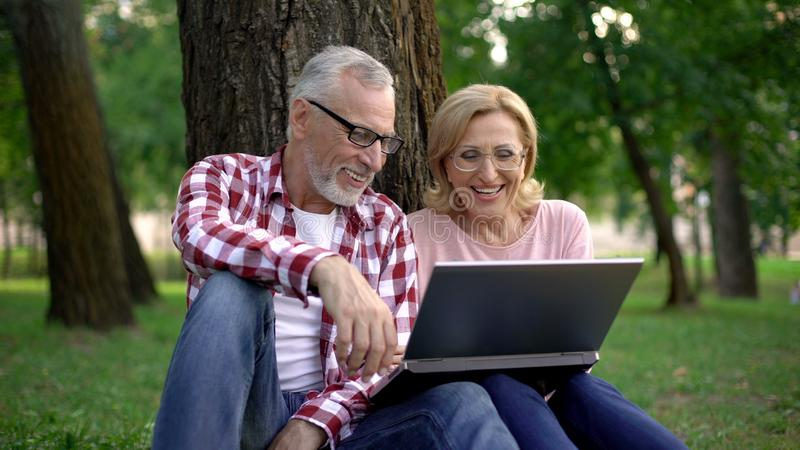 Joyful senior couple sitting in park and watching funny video on laptop computer. Stock photo royalty free stock photography