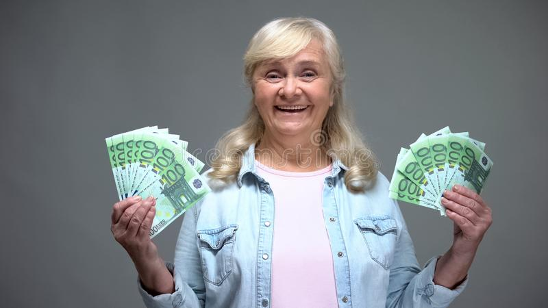 Joyful senior female showing euro banknotes, quick loan service, wealth concept stock photos
