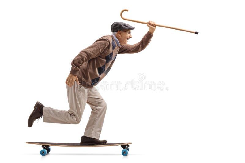 Joyful senior holding a cane and riding a longboard stock images