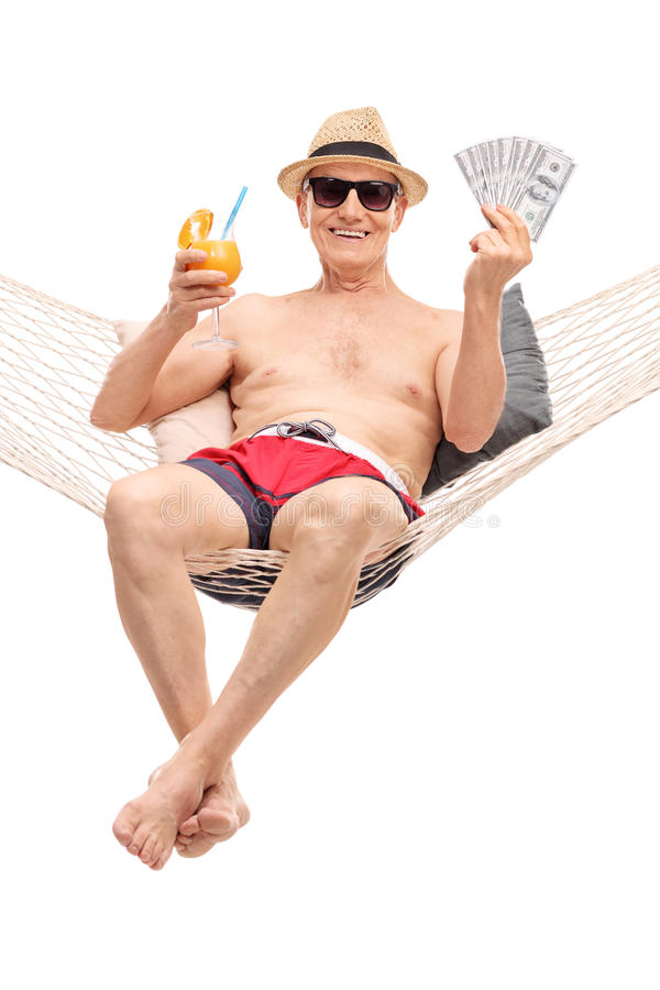 Joyful senior holing money seated in a hammock. Vertical shot of a joyful senior man in a swim trunks drinking a cocktail and holing a stack of money seated in a royalty free stock photo