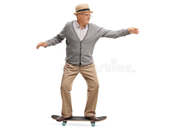 Joyful senior man riding a skateboard. Isolated on white background royalty free stock photo