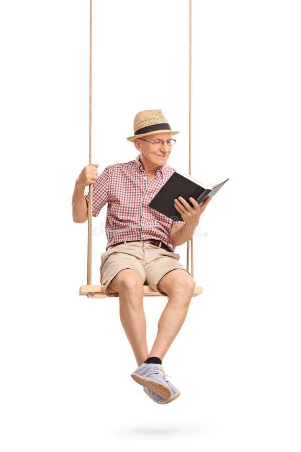 Joyful senior sitting on swing and reading a book stock images