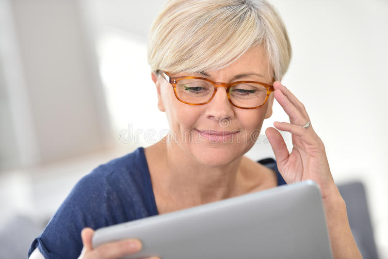 Joyful senior woman using tablet stock photo