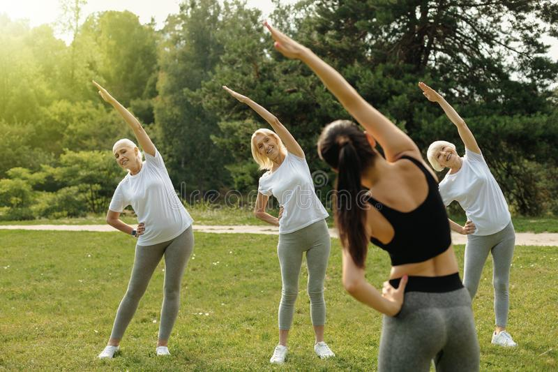 Joyful senior women taking part in group training session royalty free stock photo