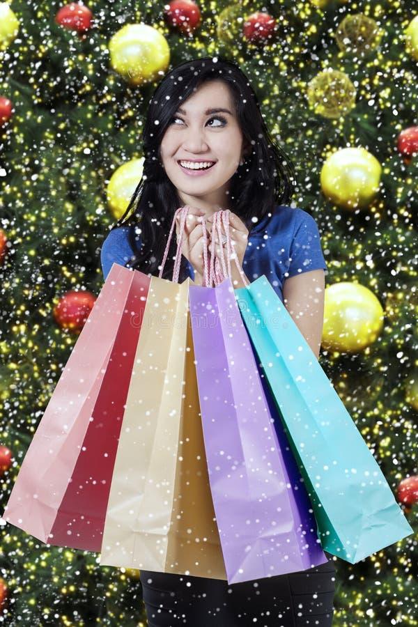 Joyful shopper holds christmas shopping bags royalty free stock images