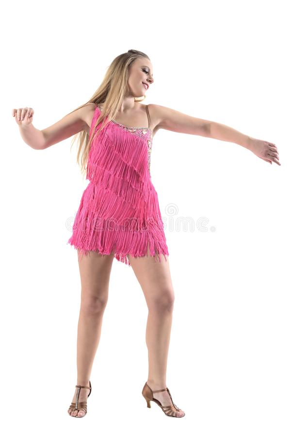Joyful smiling caucasian woman dancing Latino dances in pink fringe dress. Full body length portrait isolated on white studio background royalty free stock image