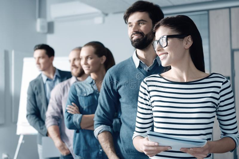 Joyful smiling woman standing with her colleagues in the office royalty free stock images