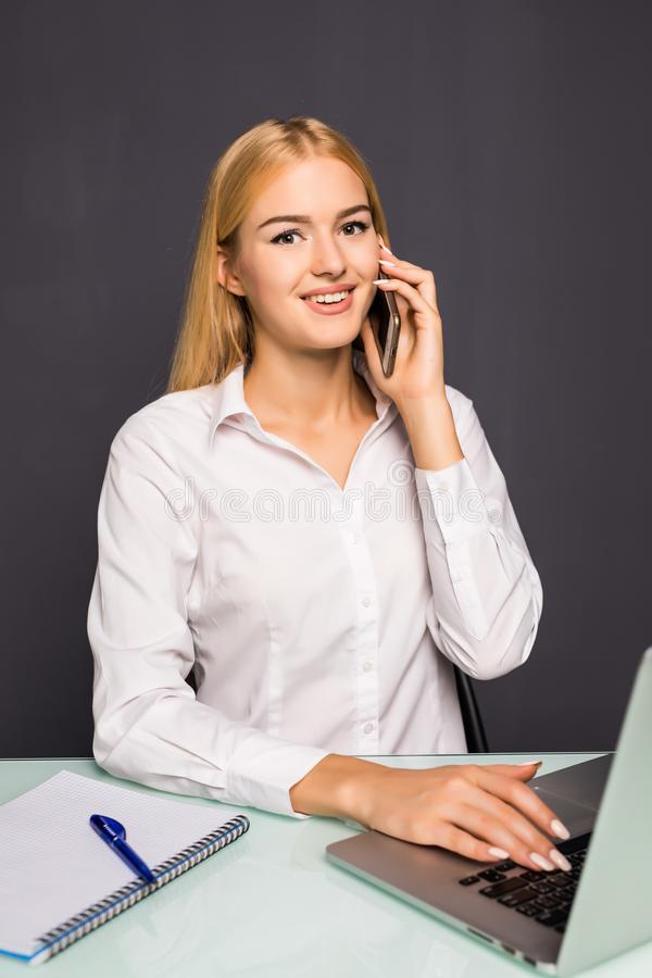 Joyful smiling young woman having talk by phone in office. Joyful smiling young woman having negotiations by phone in office royalty free stock image