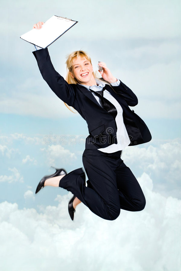 Joyful stewardess. Vertical photo of very happy woman in high jump with documents and cell in hands up in the clouds royalty free stock photo