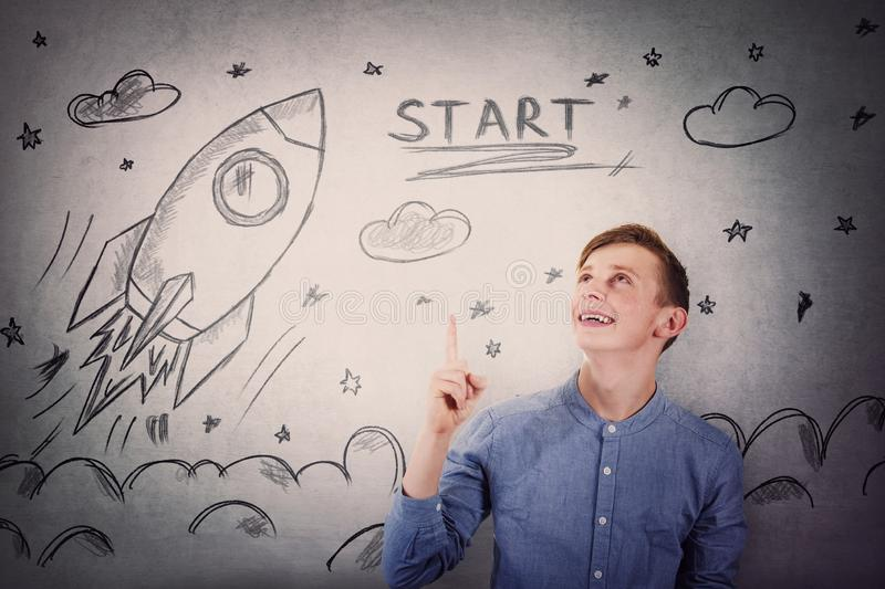 Joyful student guy pointing finger and looking up, happy face expression, showing rocket ship startup sketch, taking off in space.  stock photo