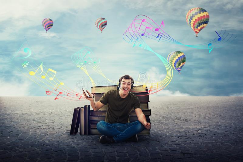 Joyful student guy seated relaxed on the floor listening to a song on headphones stock photos