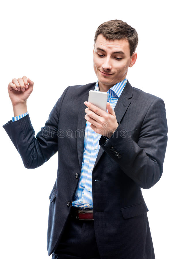 Joyful successful businessman with a phone in hands on a white. Background stock image