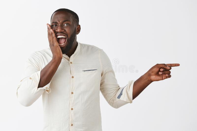 Joyful and talkative dark-skinned guy in white shirt gossiping about coworker, pointing right and whispering rumor to. Friend, being amazed and astonished with stock photos