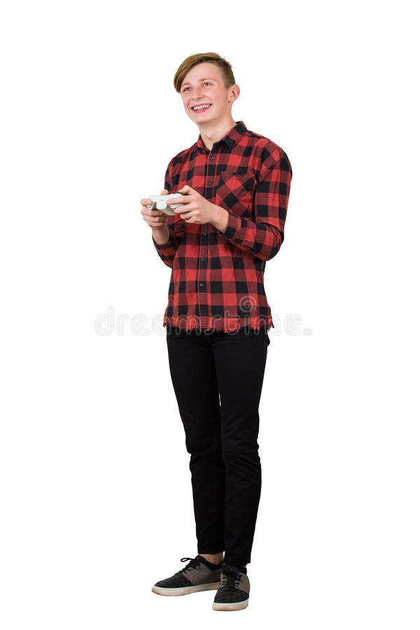 Joyful teenage boy playing video games isolated over white background. Excited guy stand all ears holding a joystick console royalty free stock photos
