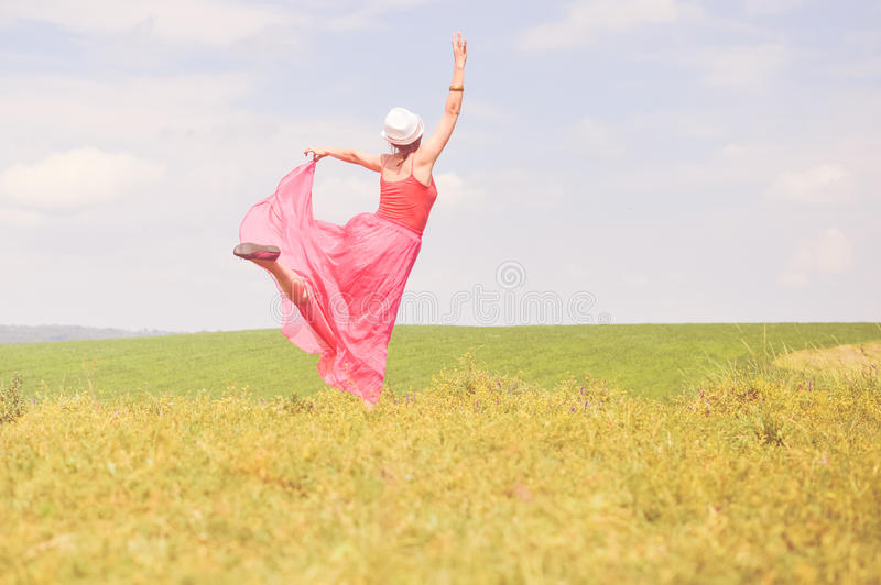 Joyful time outdoors: image of having fun elegant blond young woman in red dress happy dancing on green summer meadow copy space stock photo