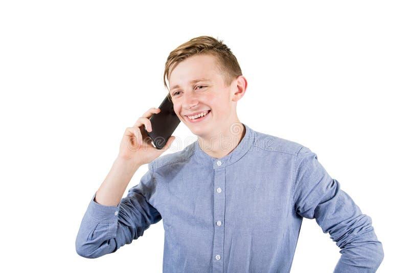 Joyful tonåring som pratar med någon på sin mobiltelefon isolerad över vit bakgrund Ungdomspojke som talar på smartphone royaltyfri bild