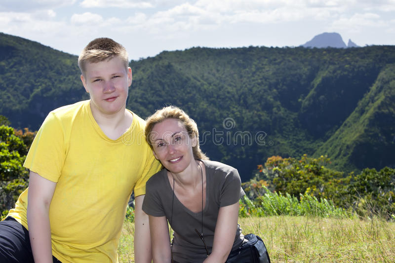 Joyful tourists on a background of mountains and the woods of Mauritius royalty free stock image