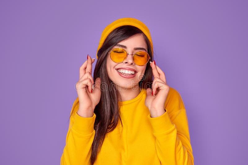 Joyful trendy woman crossing fingers with hope. Cheerful young woman in shades and beany smiling and crossing fingers with closed eyes while standing over purple royalty free stock photo