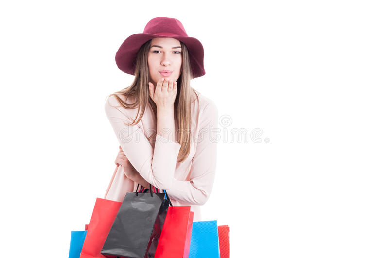 Joyful trendy woman doing shopping and blowing a kiss royalty free stock images