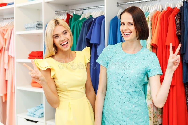 Joyful two girls making fitting in shop stock image