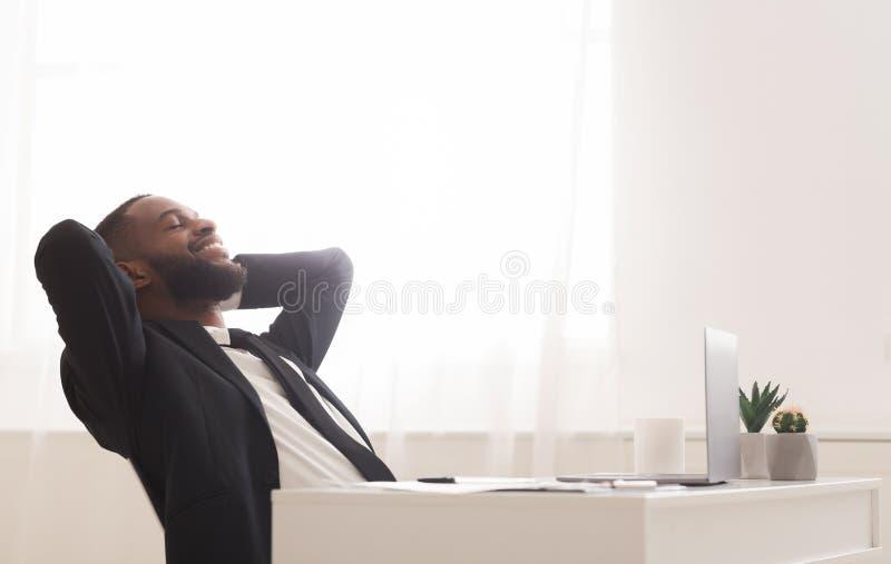 Joyful, ung chef som frigör sig från stolen på ett vitt, modernt kontor arkivbild