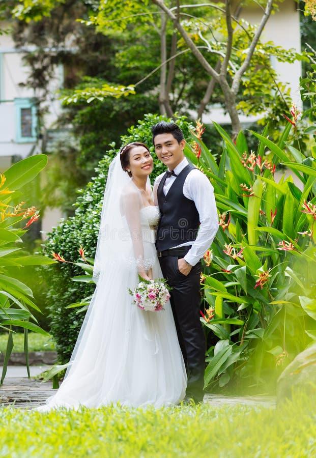 Joyful wedding couple. Full-length portrait of joyful wedding couple in the park stock photography