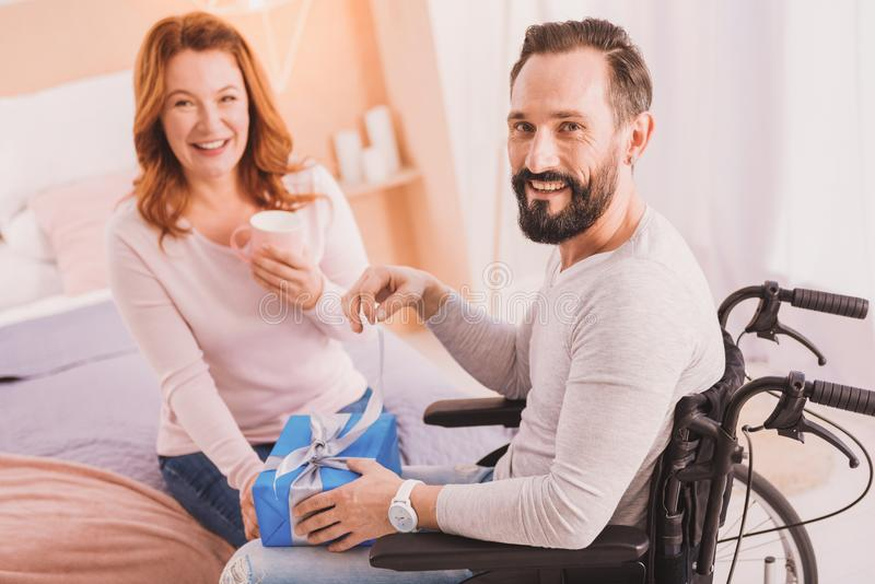 Joyful wheelchaired man opening his present. Inclusive life. Paralyzed cheerful men smiling and opening his birthday present royalty free stock photo