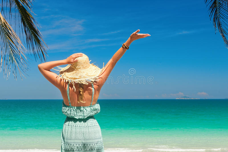 joyful woman with arm up on beach in summer during holidays travel. royalty free stock images