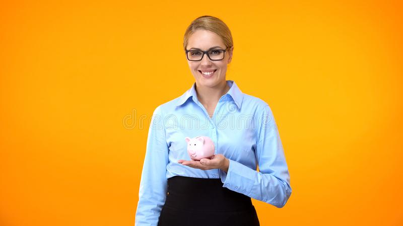 Joyful woman in formal suit holding piggybank in hand, investment profit, budget. Stock photo royalty free stock photography