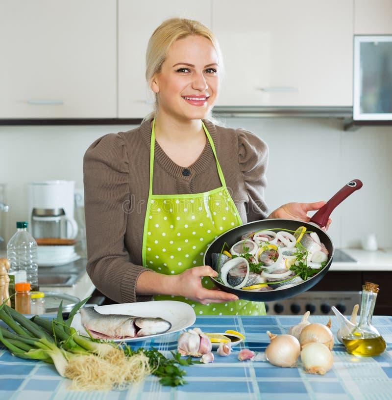Joyful woman with frying pan. Joyful woman with fish in frying pan stock photography