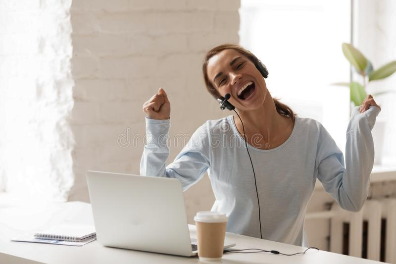 Joyful woman in headphones with microphone using laptop, sing an. Joyful woman in headphones using laptop, sing and dancing during break, moving in rhythm with stock photo