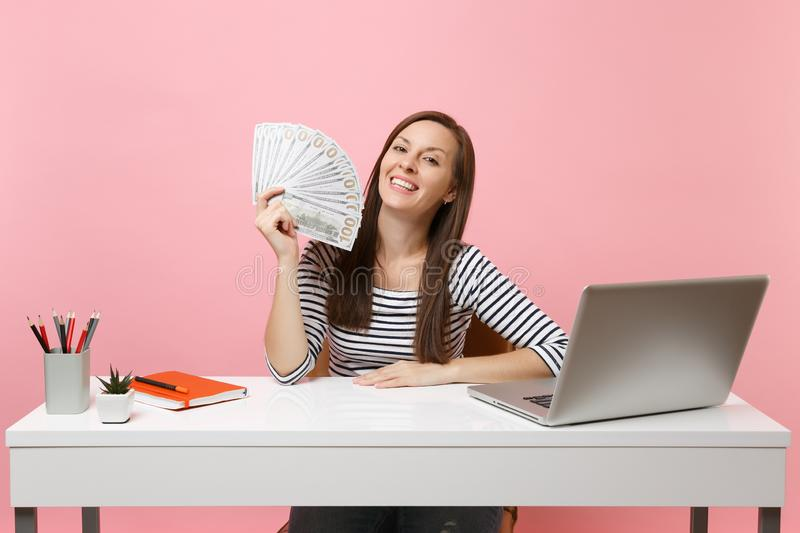 Joyful woman holding bundle lots of dollars, cash money working on project at office at white desk with pc laptop stock images
