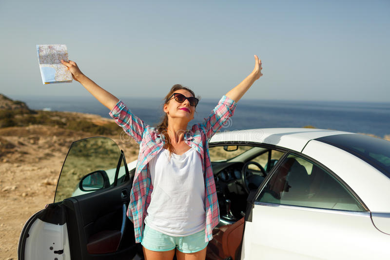 Joyful woman with a map in her hand traveling on a cabriolet royalty free stock image