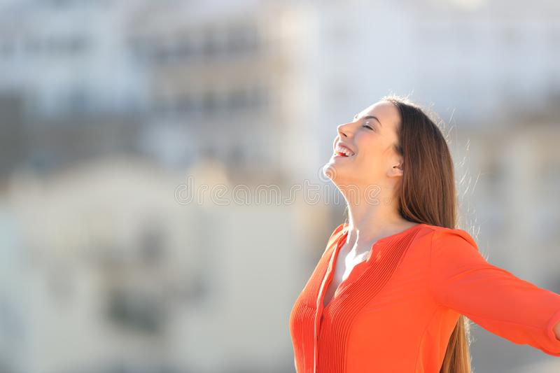 Joyful woman in orange breathing deep fresh air outdoors stock photo