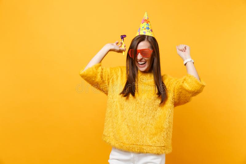 Joyful woman in orange funny glasses birthday party hat with playing pipe rising hands celebrating enjoying holiday. Isolated on yellow background. People royalty free stock image