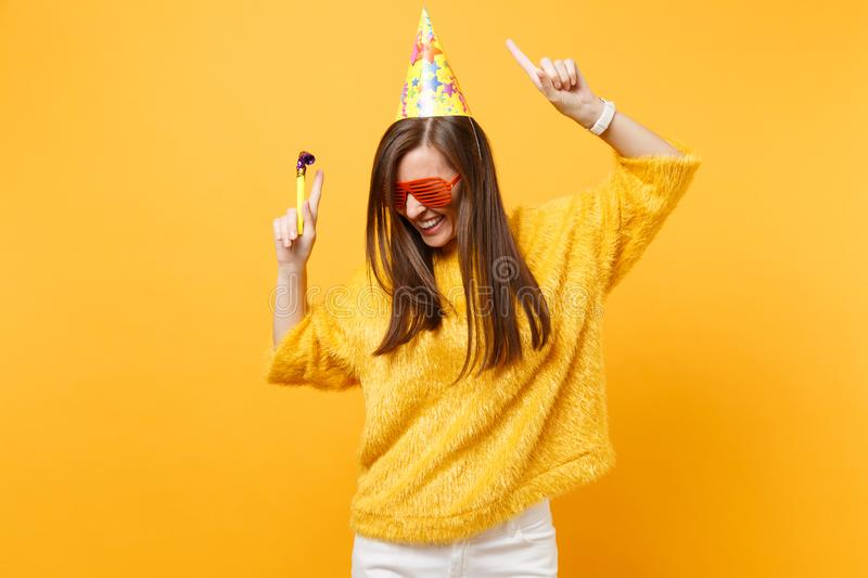 Joyful woman in orange funny glasses birthday party hat with playing pipe rising hands pointing index fingers up. Dancing celebrating isolated on yellow royalty free stock image