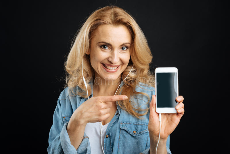 Joyful woman presenting new phone royalty free stock image