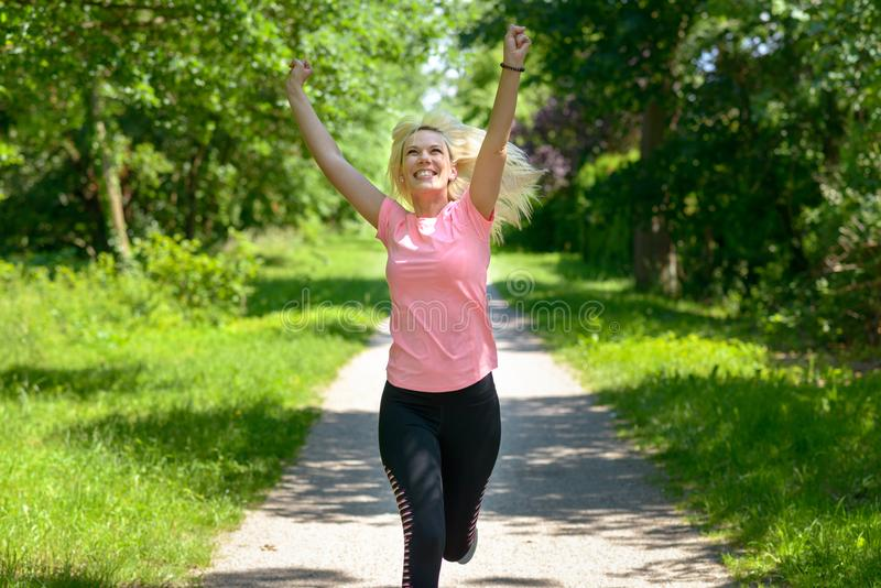 Joyful woman running along a woodland track. With her arms raised and a beaming smile as she celebrates spring royalty free stock images