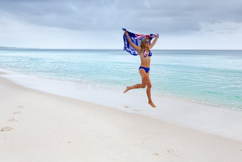 Joyful woman running with Australian flag on beach. Woman in motion as she runs along the beach holding Australian flag above her Celebrate Australia Day stock image