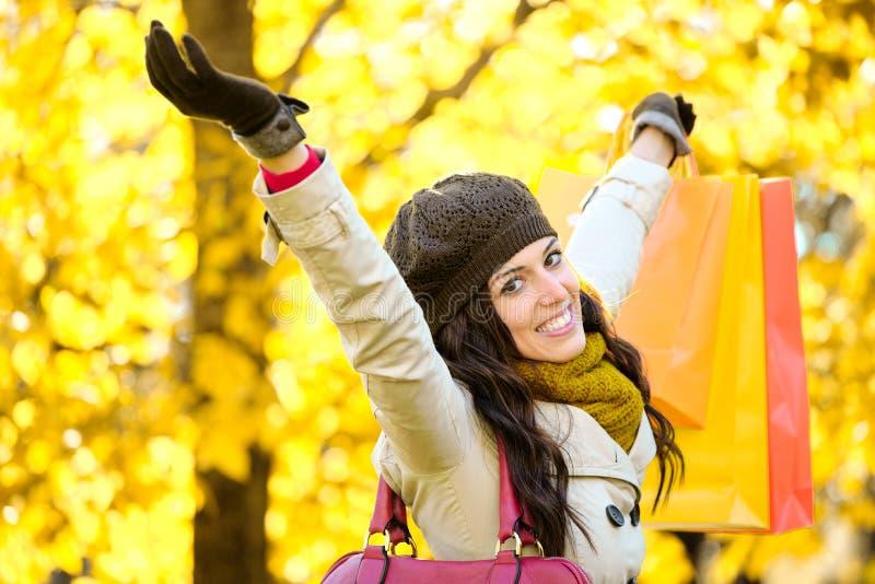 Joyful woman shopping and having fun in autumn royalty free stock photography