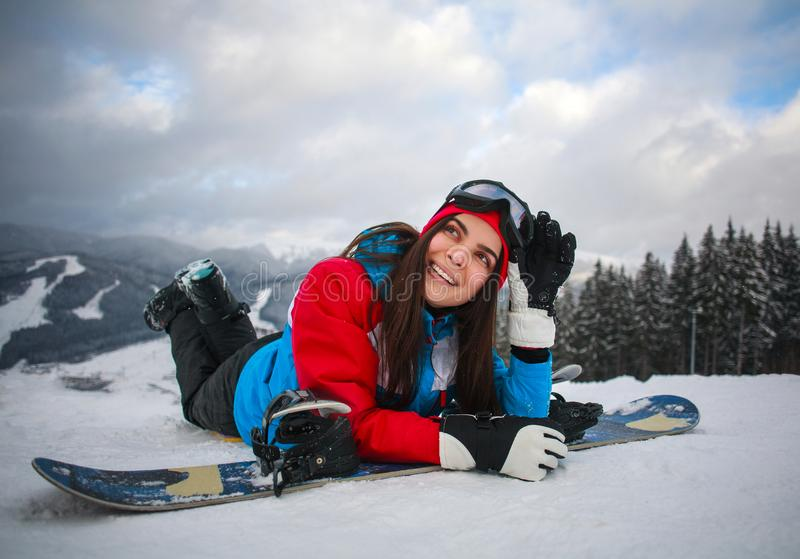 Joyful woman snowboarder in winter at ski resort royalty free stock image