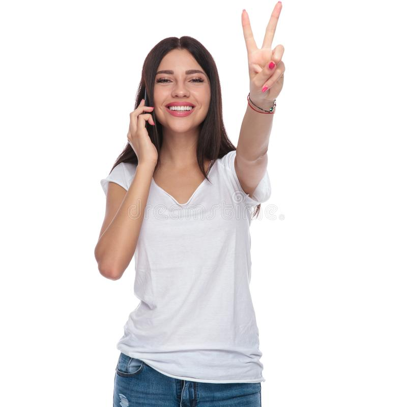 Joyful woman speaking on the phone and making victory sign royalty free stock photography