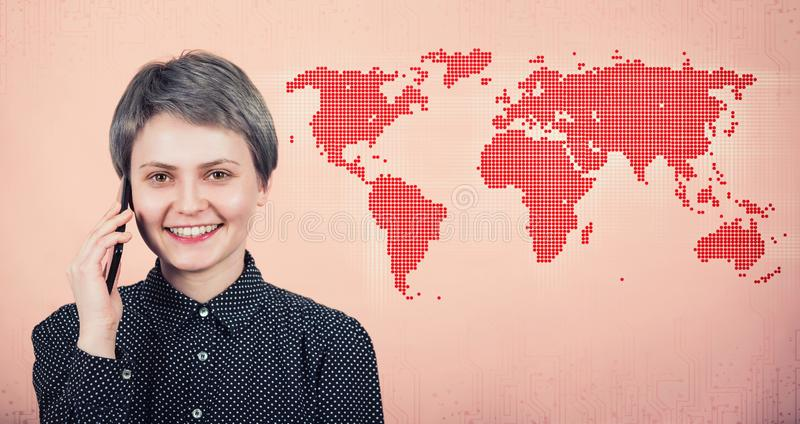 Joyful woman talking on phone abroad, smiling over pink wall with world map. Trendy positive tourist girl speak on smartphone in royalty free stock photos