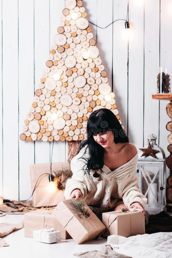 Joyful woman unpacking Christmas gifts stock photo