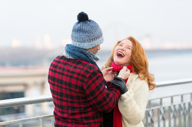 Joyful woman loves date. Guy make funny woman in red scarf. Rouge woman laughing in city. With man who care her royalty free stock photography
