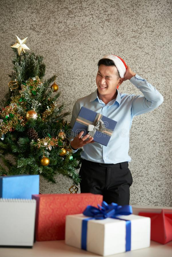 Opening presents. Joyful young Asian entrepreneur scratching nape when opening boxex from secret Santa stock images