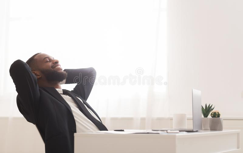 Joyful young manager relaxing on chair in white modern office. Joyful young black manager relaxing on chair in white modern office, leaning back with closed eyes stock photography