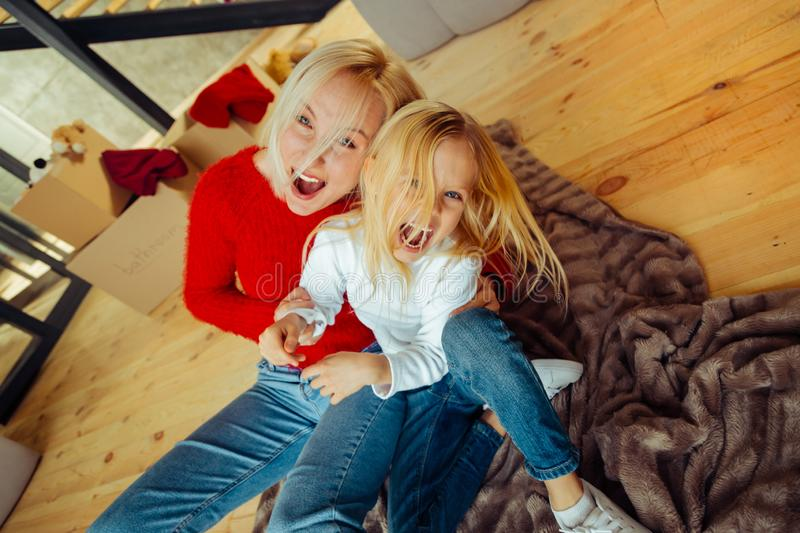 Joyful young blonde woman embracing her daughter royalty free stock images