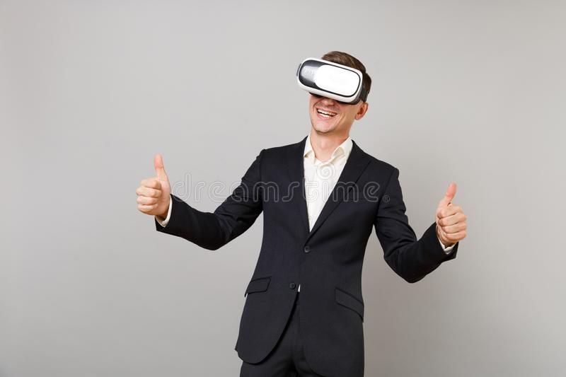 Joyful young business man in classic black suit, shirt looking in headset, showing thumbs up isolated on grey wall. Background in studio. Achievement career stock image