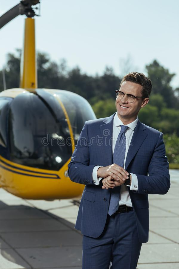 Joyful young businessman waiting for a helicopter pilot royalty free stock photos